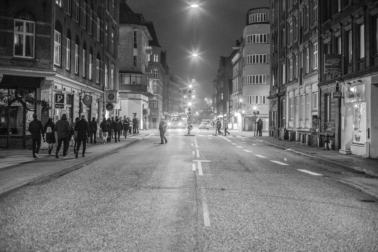 architecture, city, street, building exterior, built structure, night, illuminated, building, street light, direction, the way forward, city life, transportation, road, crowd, group of people, city street, diminishing perspective, large group of people, real people