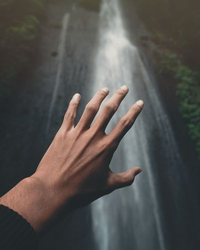 Close-up of hand against waterfall