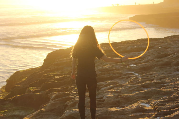 Silhouettes Beach Beauty In Nature Day Full Length Hula Hoop Hula Hooping  Hulahoop Leisure Activity Lifestyles One Person Outdoors People Real People Rear View Sand Scenics Sea Silhouette Silhouette In Motion Sky Standing Sunlight Sunset Water Paint The Town Yellow Second Acts