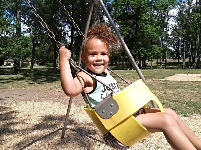 Portrait of girl swinging in swing at park