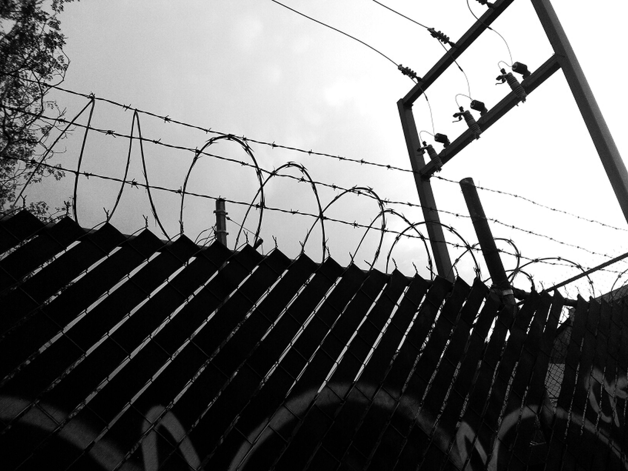 low angle view, sky, silhouette, built structure, metal, architecture, building exterior, fence, metallic, chainlink fence, outdoors, no people, clear sky, day, cloud - sky, cloud, protection, dusk, safety, construction site
