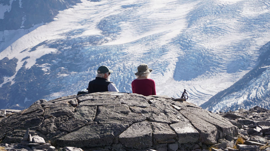 Rear view of people sitting on snowcapped mountain