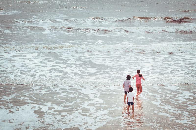 Rear view of people walking in calm sea