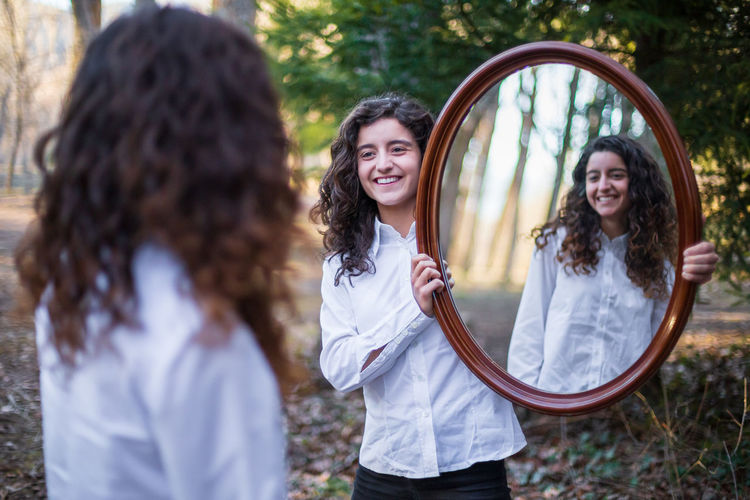 Smiling young woman holding mirror for sister in forest