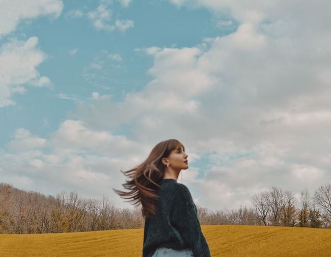 Young woman looking away while standing on field against sky