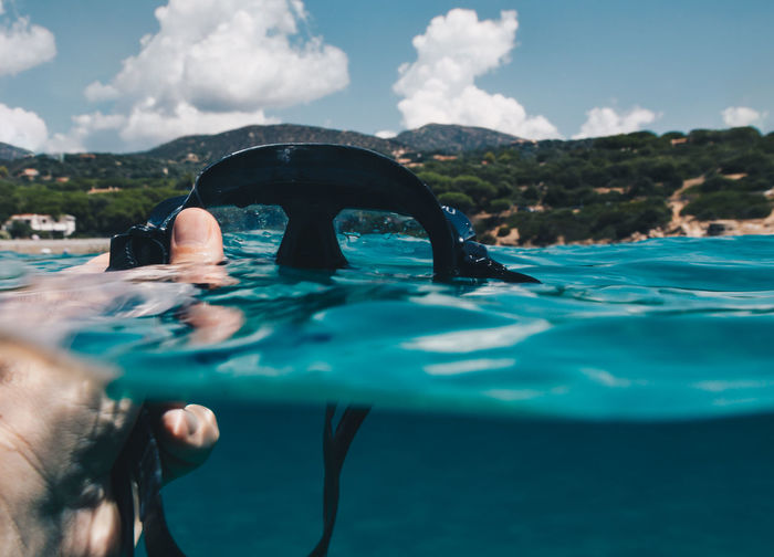 Cropped hand of man holding scuba mask in sea