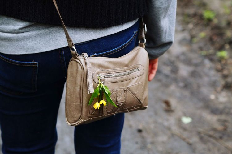 Spring flowers attached to a leather purse Casual Clothing Midsection Holding One Person Day Real People Standing Outdoors Flower Close-up People Purse Woman Flowers Spring Paint The Town Yellow
