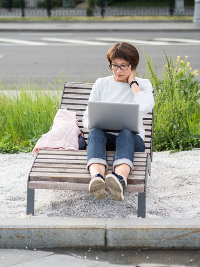 Full length of man using mobile phone while sitting on bench