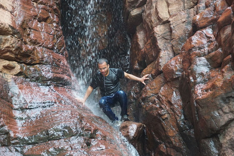 Man Enjoying Waterfall Amidst Rock Formations In Forest