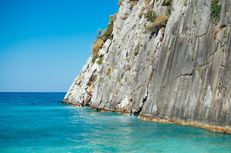 Rock formation in sea against clear blue sky