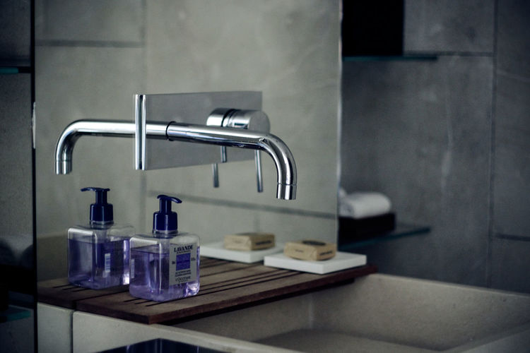 Faucet and soap dispenser in bathroom at home