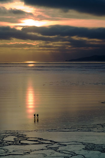 TWO DISTANT PEOPLE WALKING ON BEACH AT SUNSET