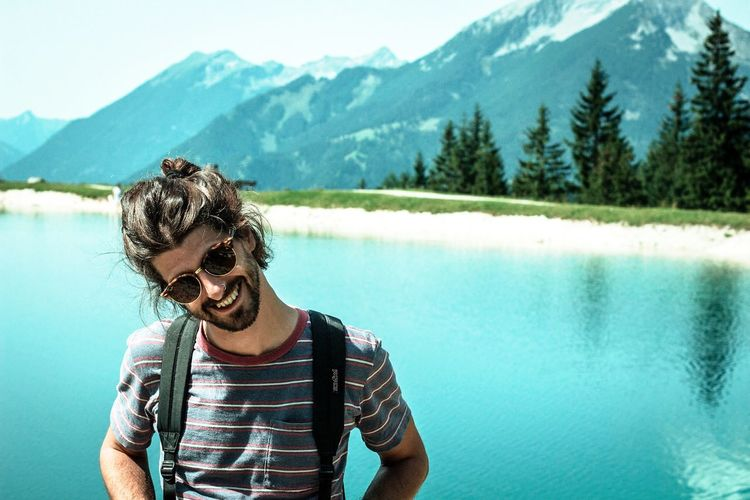 young man with sunglasses at a mountain lake in summer Recreation  Retreat Bun Manbun Dark Hair Beard Smiling Face Smiling :) Tranquil Scene Holidays Pond Smiling Happiness Young Adult Mountain Cheerful Fun Water Nature Enjoyment Lifestyles Outdoors Beauty In Nature Young Men Real People Adult Day Vacations One Person Portrait An Eye For Travel Love Yourself Summer Exploratorium