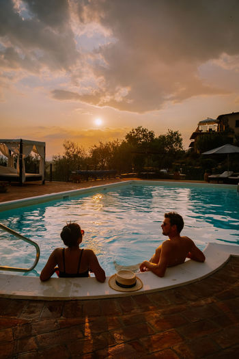 People relaxing in swimming pool against sky during sunset