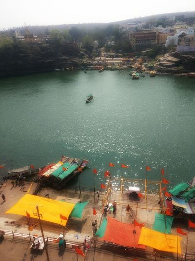Banks of river Holy Place Narmada River Old Clothes As Shelters Flower Market Boat Rides Water Lives Making Best Out Of Life Simple Living colirfulview from top