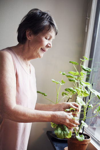Woman holding while standing by potted plant at home
