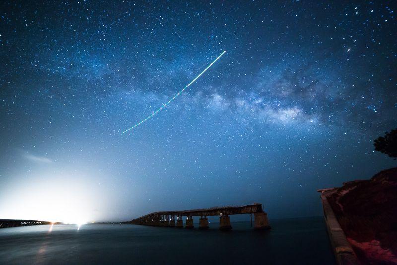 Abandoned bridge over sea against star field