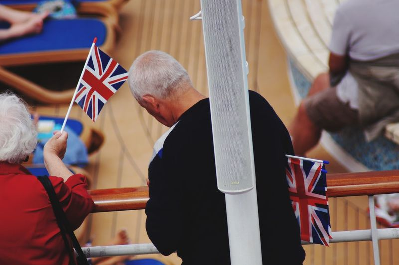 Senior people with british flags standing on ship