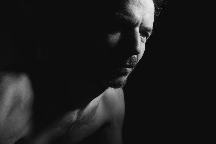 Close-up portrait of shirtless man against black background