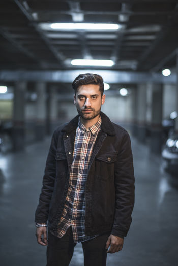 Portrait of young man standing in underground parking lot