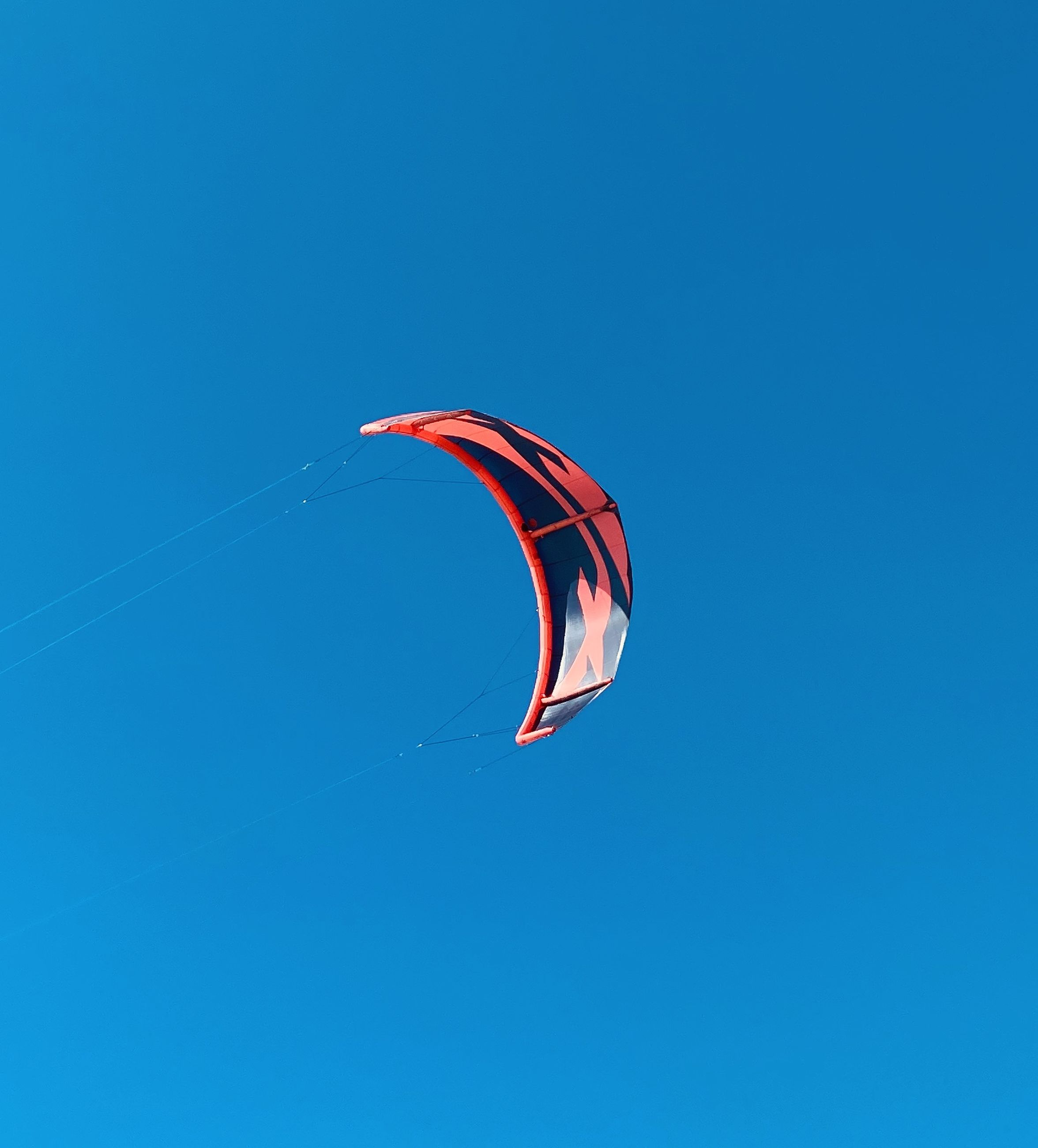 blue, windsports, sports, sky, flying, clear sky, mid-air, toy, nature, low angle view, paragliding, parachute, extreme sports, adventure, leisure activity, copy space, day, kite sports, joy, motion, sunny, sport kite, environment, outdoors, kite - toy, wind, transportation, gliding, multi colored, no people, exhilaration