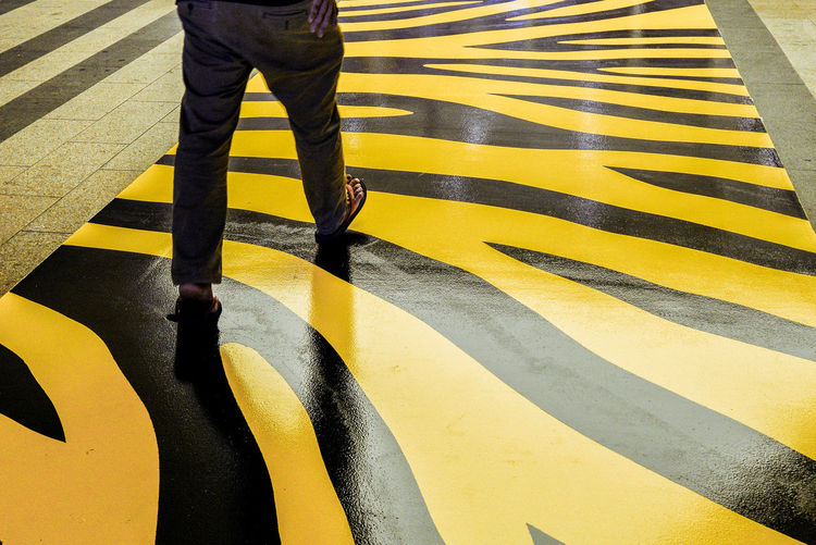 Low section of man walking on patterned zebra crossing