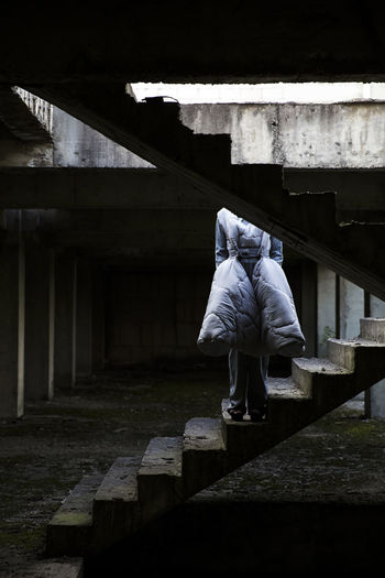 Rear view of woman standing on staircase in abandoned building