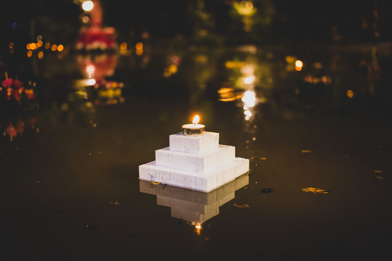 Illuminated tea light candle on built structure in lake at night