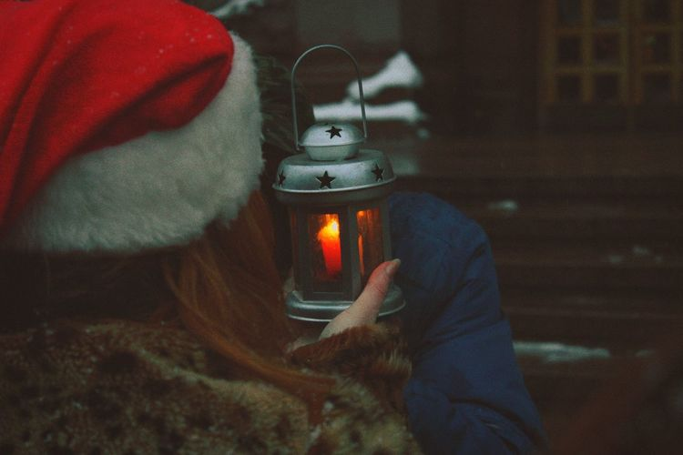 Rear view of woman holding illuminated lantern with friend during winter