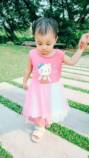 Cute girl standing on footpath