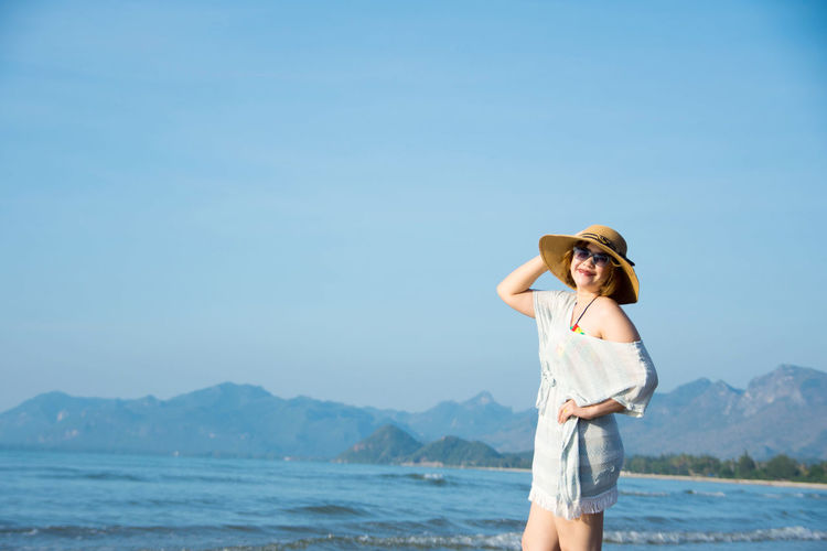 Smiling woman wearing sunglasses and hat against blue sky at beach