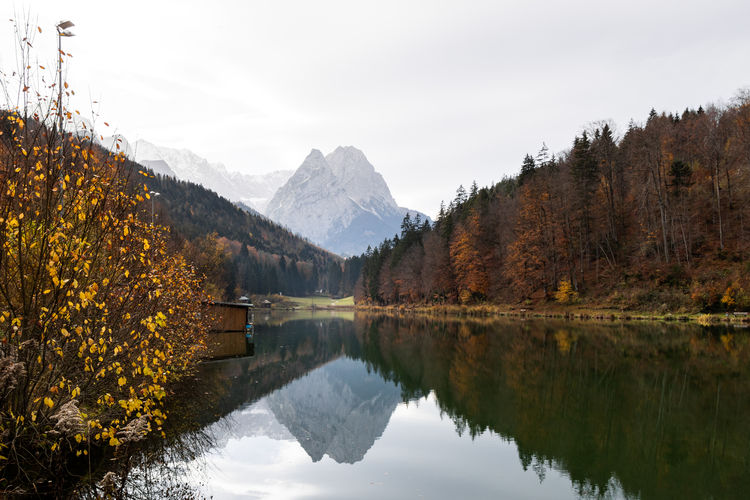 Beautiful autumn colors with calm lake at a Lake Riessersee in Garmisch-Patenkirchen, Bavaria, Germany. Reflection Beauty In Nature Mountain Water Lake Tranquility Scenics - Nature Tranquil Scene Tree Sky Plant Nature Mountain Range Non-urban Scene Day No People Waterfront Idyllic Outdoors Change Autumn Lake Autumn colors Autumn Leaves Refelction  Calm Water My Best Photo