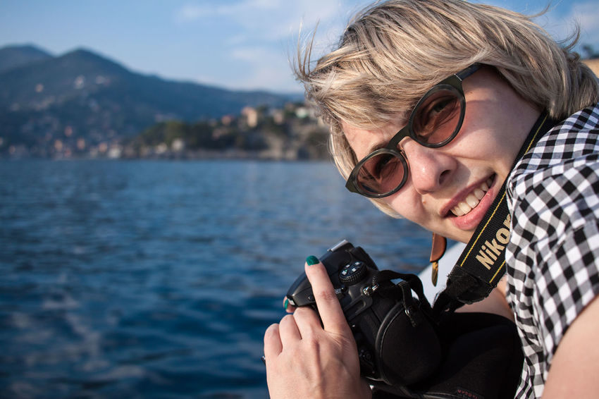 Adult Camera - Photographic Equipment Eyeglasses  Focus On Foreground Happiness Holding Mountain Nature One Person Outdoors Photographer Photographing Portrait Real People Sea Sea And Sky Sky Smiling Technology Water Second Acts
