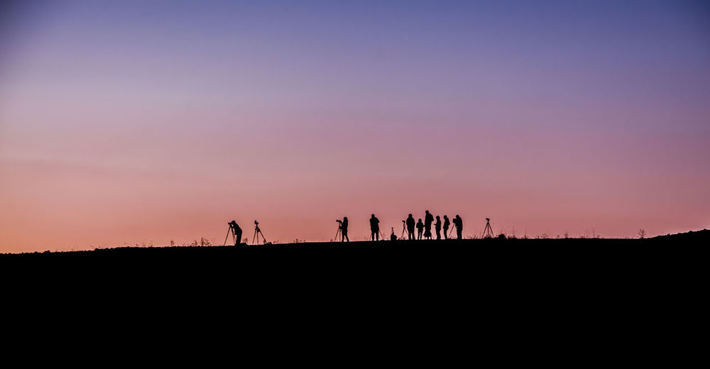Silhouette People On Landscape At Sunset