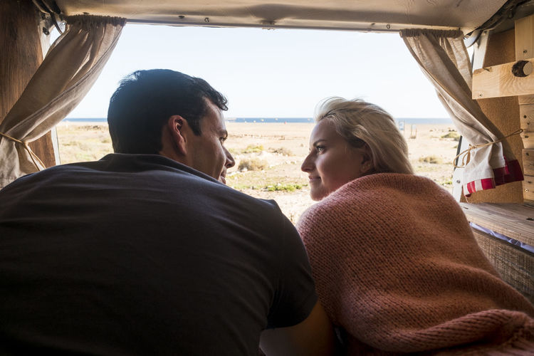 Rear view of couple lying in camper trailer