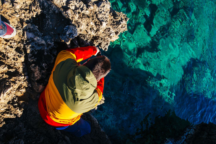 High angle view of man sitting on rock formation by sea