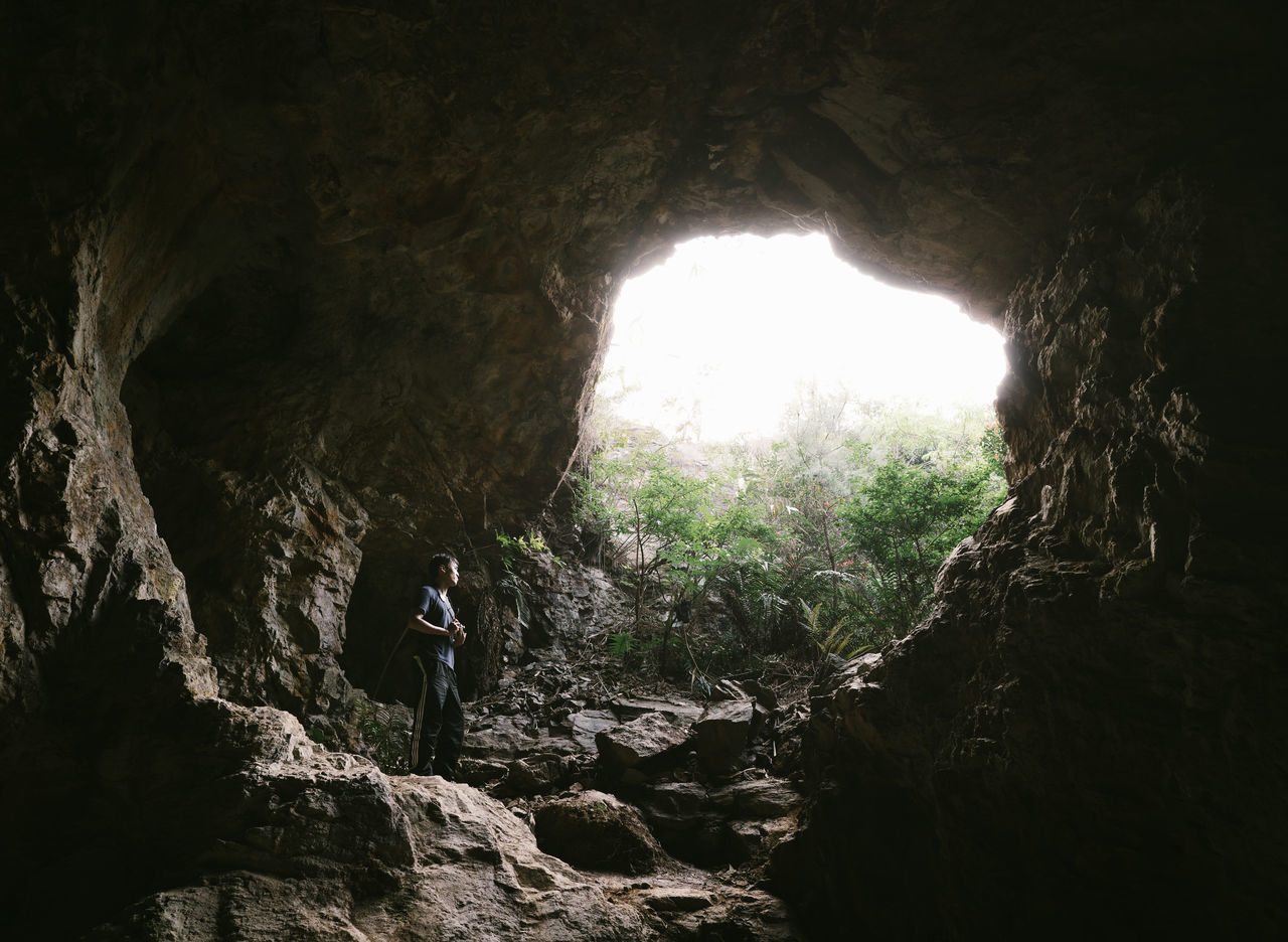 rock - object, real people, cave, rock formation, nature, one person, adventure, day, forest, full length, hiking, leisure activity, tunnel, indoors, tranquility, exploration, beauty in nature, tree, lifestyles, standing, people