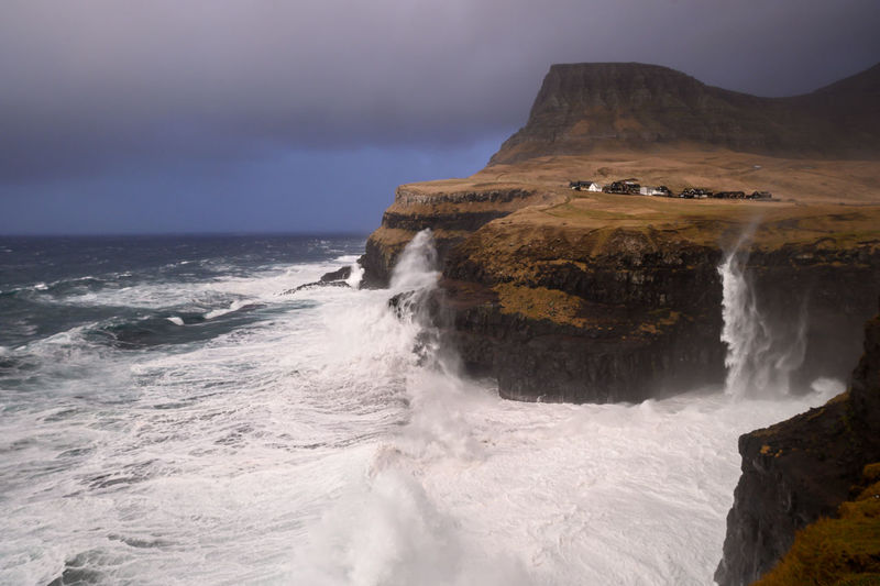 Scenic view of  gitated sea against cliffs. féroé islands landmark.