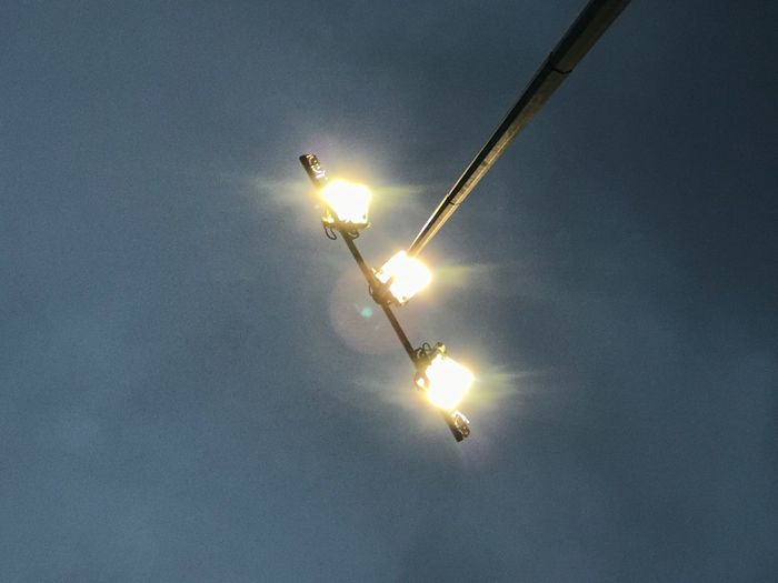 Low angle view of illuminated sun against sky