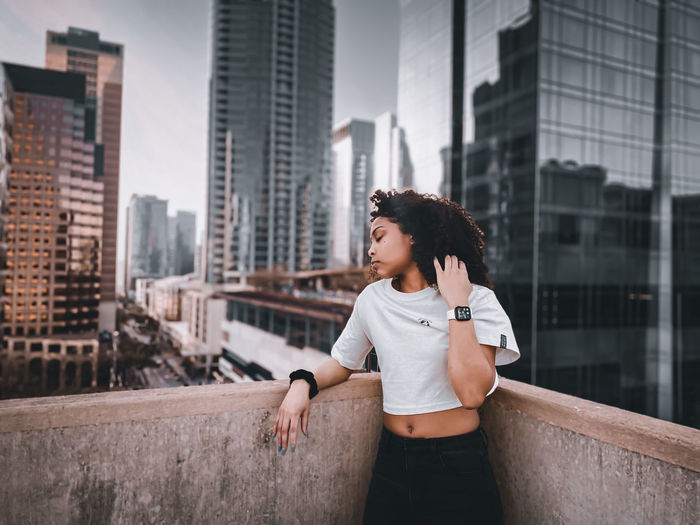 Young woman looking away against buildings in city