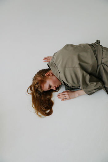 Casual Clothing Indoors  Portrait Girls Studio Shot One Person Females Copy Space Lifestyles Hairstyle Fashion Fashion Model Young Women Females Female Lying Down Trench Coat Ginger Redhead Redhair Gingerhair Messy Weird