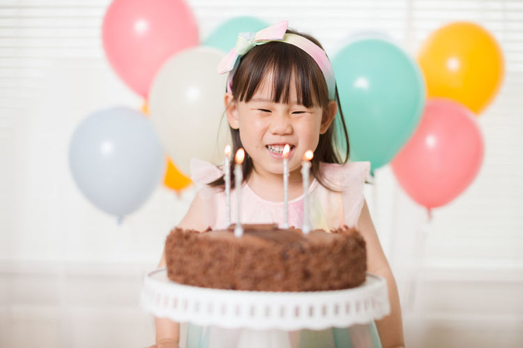 Young girl blowing candles for celebreating her 4th years birthday