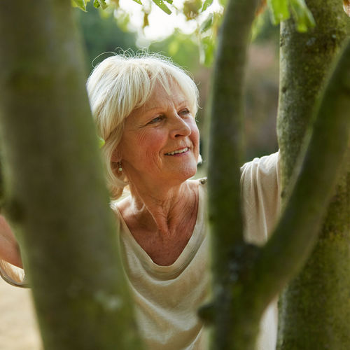Senior Woman Looking Away By Trees