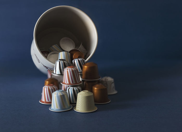Coffee Blue Blue Background Capsule Choice Close-up Colored Background Currency Finance Food And Drink Indoors  Large Group Of Objects No People Rolled Up Silver Colored Stack Still Life Studio Shot Sweet Sweet Food Table Temptation Variation