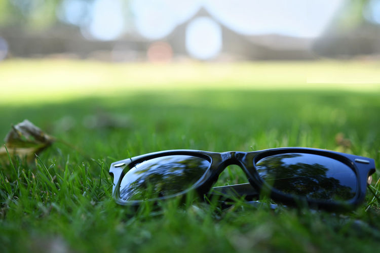 Close-up of sunglasses on field