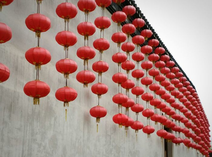Low angle view of chinese lanterns hanging by wall