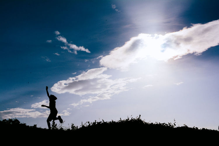 Low Angle View Of Silhouette Boy Jumping Against Blue Sky