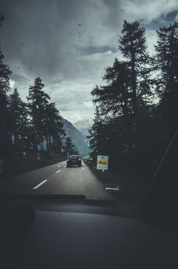 Accidentally in the middle of the Tour de Swiss driving behind the Cars :) Switzerland Trip Summer 2017. EyeEmNewHere Car Car Interior Cloud - Sky Day Eye4photography  First Eyeem Photo Land Vehicle Mode Of Transport Nature No People Outdoors RainDrop Road Sky Street Switzerland The Way Forward Tour De Suisse Transportation Tree Water Weather Wet Windshield