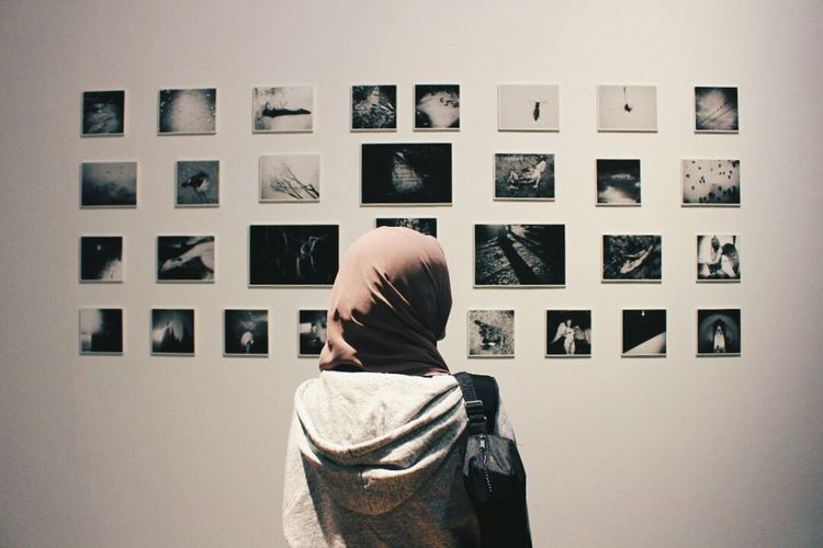Rear view of woman standing against wall