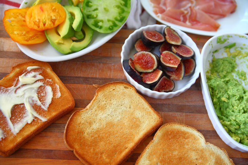 Toast and ingredients for prosciutto sandwich Food Healthy Eating Freshness Indoors  No People Close-up Breakfast Toast Fig Avocado Heirloom Tomatoes Dishes Food Preparation Overhead Flat Lay Homemade Food Mayonnaise Fresh Produce Natural Light Vegetables Cutting Board Textures Brunch